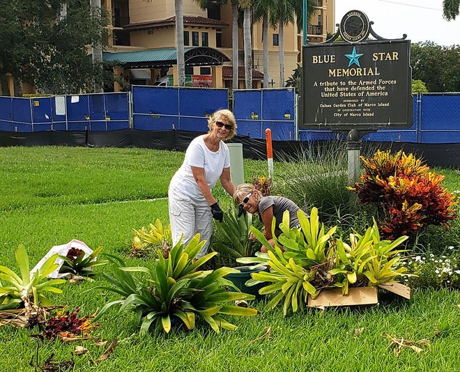 Linda Colombo and Margie Bramel work to remove the Blue Star Memorial.