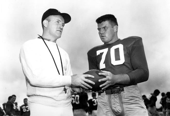 In this September 1958 file photo, Notre Dame football coach Terry Brennan, left, talks with tackle Bronko Nagurski Jr. during practice in South Bend, Ind. Brennan, a star halfback on three unbeaten Notre Dame teams who was hailed as a wunderkind when he succeeded Irish coaching great Frank Leahy at just 25 years old, has died. He was 93.