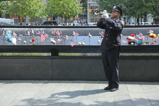 NYPD Officer Michael Campagno plays Taps after the last name was read at the conclusion of the ceremony. The September 11 Commemoration Ceremony marks the 20th Anniversary of the attacks that took place on 9/11. The ceremony took place on the 9/11 Memorial Plaza at the World Trade Center site in lower Manhattan, NY on Sept 11, 2021.