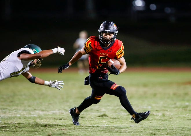 Palm Desert's Hanyi Joh (5) runs wide as Murrieta Mesa's Juan Diego Aguilar (18) dives to try and make a tackle during the second quarter of their game at Palm Desert High School, Friday, Sept. 10, 2021, in Palm Desert.