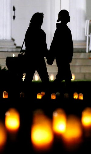 A couple holds hands as they take in the 2,976 candles on display at the Tallmadge Circle Saturday night on the 20th anniversary of the 9/11 terror attacks. Every year, the Tallmadge Fire Department lights a candle for every person who died on 9/11 in the terrorist attacks on the World Trade Center, the Pentagon and Flight 93.