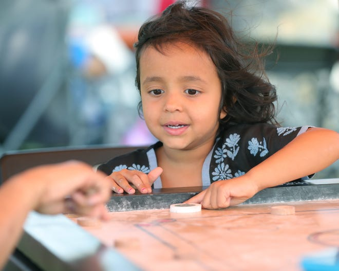 Arya Hickey 4, gets instruction from her grandmother Rama Srinivasan while playing a board game at IndiaFest  Sunday in Jackson Township. [Phil Masturzo/ Beacon Journal]