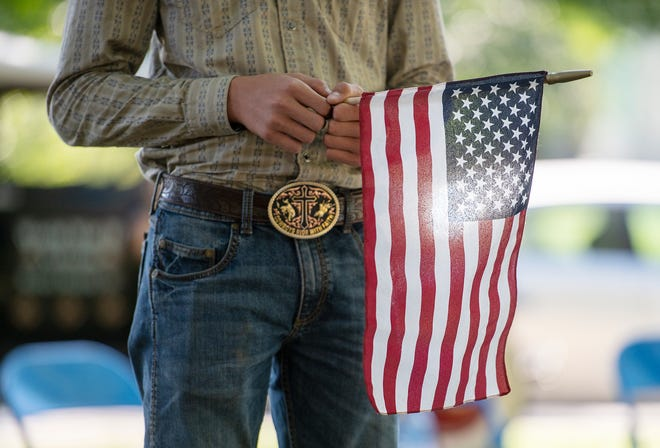 Sean Justice, 15, of Brighton Township holds a flag during a 9/11 ceremony at Irvine Park Saturday afternoon in Beaver.