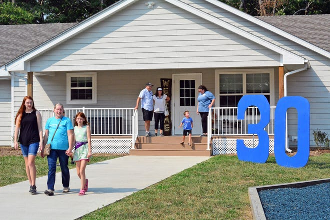 Visitors exit the Ubl House on Saturday during the 30-year anniversary celebration of Coyote Hill Foster Care Neighborhood. The Ubl House is the seventh house to open on Coyote Hill's 300-acre campus near Harrisburg.