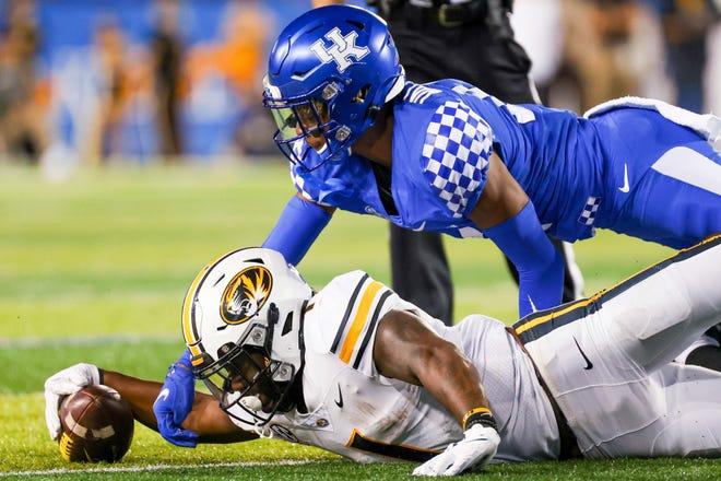 Kentucky defensive back Carrington Valentine, top, tackles Missouri running back Tyler Badie during the second half Saturday night.