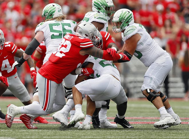 Ohio State Buckeyes defensive tackle Haskell Garrett (92) makes a tackle of Oregon Ducks running back Travis Dye (26) in the first quarter of their NCAA Division I game on Saturday, September 11, 2021 at Ohio Stadium in Columbus, Ohio.