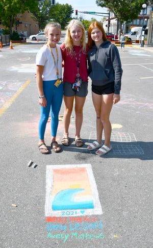 Kendra Brekken, Brea Lessard and Avery Mathews stand next to their Instagram-worthy chalk drawing during Chalk It Up 2021 downtown