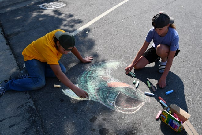 CHS Kiwanis Builders Club students do a chalk drawing of a bass