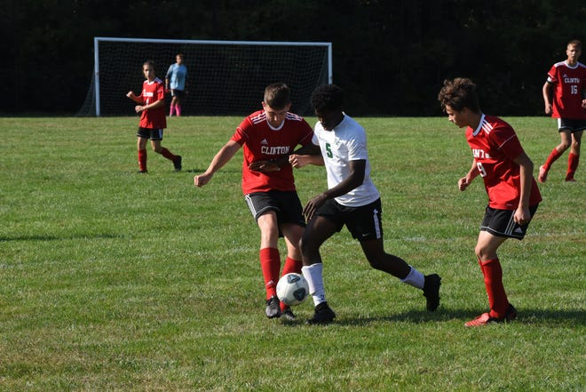 Clinton's Bryce Wyman, left, and Sylas Montgomery (9) battle with Ypsilanti Arbor Prep's Patrick Combo (5) for control of the ball during Saturday's game in Clinton.