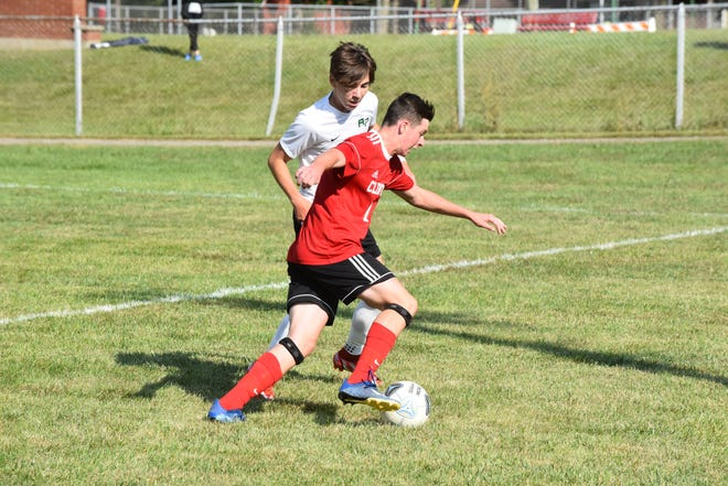 Clinton junior forward Ryan Tschirhart, foreground, moves the ball up field against an Ypsilanti Arbor Prep defender during the Redwolves 4-0 victory on Saturday morning.