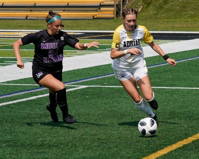 Adrian College's Mckenna Mahoney (right) moves the ball against Mount Union's Lauren Francescone (24) during Saturday's game at Docking Stadium.