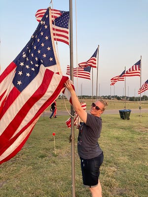 Nicole Nagel lowers a flag at Maple Grove Cemetery in Dodge City, remembrance of the lives lost on Sept. 11, 2001 on Saturday.