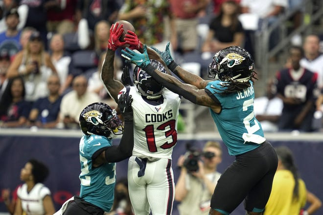 Houston Texans wide receiver Brandin Cooks (13) catches a pass for a first down as Jacksonville Jaguars' Tyson Campbell (32) and Rayshawn Jenkins (2) defend during the first half last week's game in Houston.