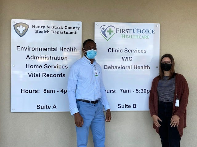 Monday Ogbeibor and Ali Brown stand in front of the listing of services available at the Clinic offices at 110 N. Burr St. in Kewanee.
