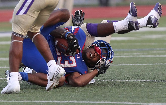 Hutchinson Community College's Corey McKnight's (23) helmet comes off as he is tackled by Butler's Quijoun Gordon (3) during their game Saturday night at Gowans Stadium. HCC lost to Butler 43-23.