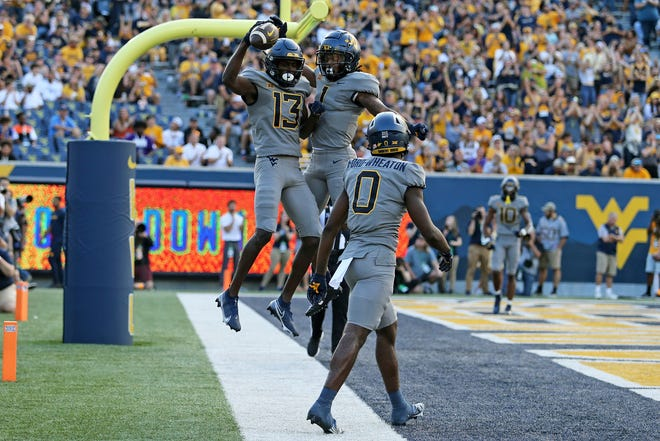 West Virginia wide receivers Sam James (13) and Winston Wright Jr. (1) celebrate after a touchdown against Long Island during the first half of an NCAA college football game in Morgantown, W.Va., Saturday. WVU won 66-0.