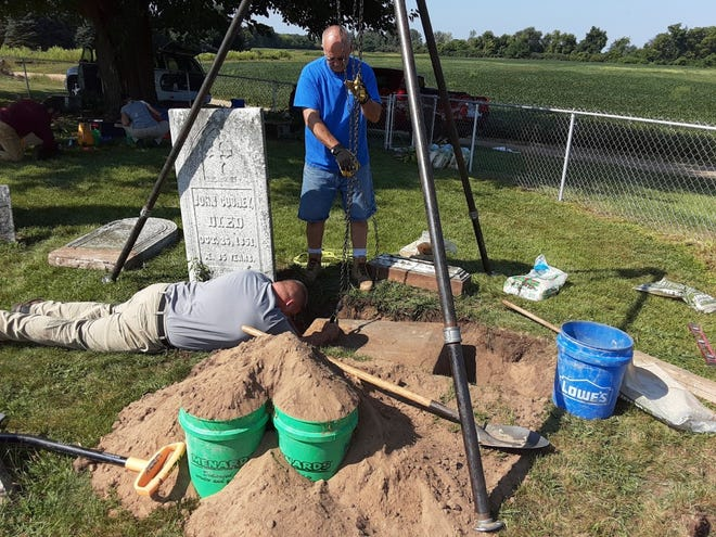 David Carter (standing), owner of Carter Cemetery Preservation, holds a pulley from a large tripod while employee Rick Weidner lies on the ground to help lift a gravestone piece that sunk in the ground at the historic St. John Catholic Cemetery in LaSalle.