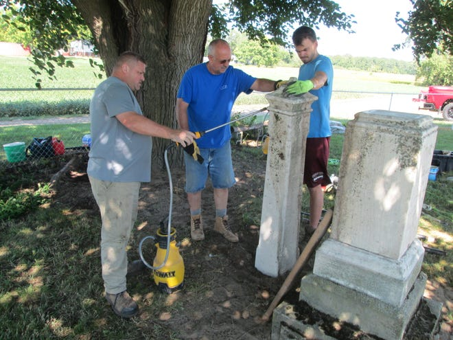 Dave Carter (center), owner of Carter Cemetery Preservation, holds up a headstone for John McCarty while employees Rick Weidner (left) and Al Weikel use a water sprayer and a nylon brush to clean and scrub dirt from the marker that fell in the St. John Catholic Cemetery in LaSalle. The headstone for McCarty, who died in 1880, fell from the marble monument sitting next to it. The marker was one of about 20 raised and restored in the old Irish cemetery maintained by St. John Catholic Church.