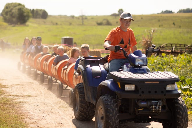 Sam Ripley, owner of Sam's Pumpkin Patch, gives barrel train rides around the farm on his opening weekend.