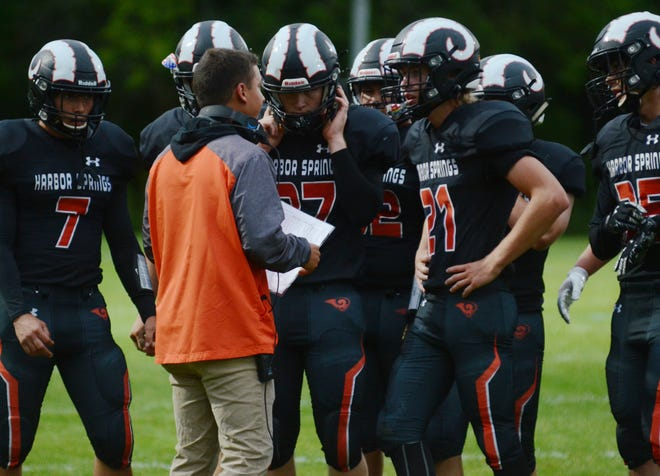 Head coach Emmet Fineout (middle) and the Harbor Springs football team can breath a sigh of relief after picking up win No. 1 on Friday.