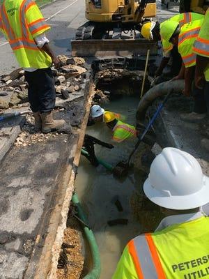 Petersburg utility workers examine the broken water line on West Washington Street in Petersburg Saturday, Sept. 11, 2021.