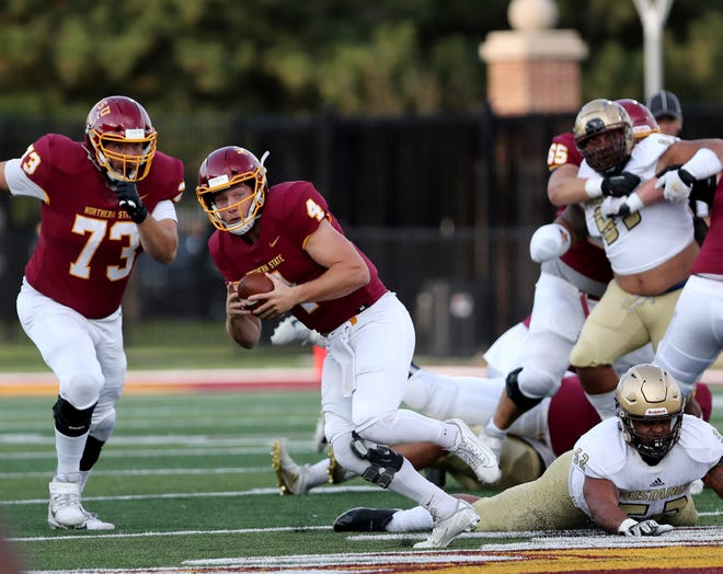 Northern State quarterback Hunter Trautman escapes from Southwest Minnesota State defensive tackle Cam Irvin to run with the ball in the first quarter of the home opener at Dacotah Bank Stadium. American News photo by Jenna Ortiz, taken 09/11/2021.