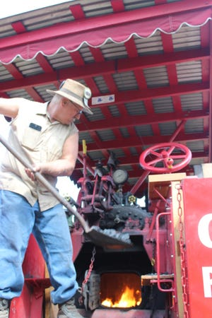 David Kroa of Niles, Michigan, comes to the jubilee every year to help the Miller family with their Gaar Scott steam engine. Here, he fires the engine with coal on Saturday before he takes a trip around the grounds.