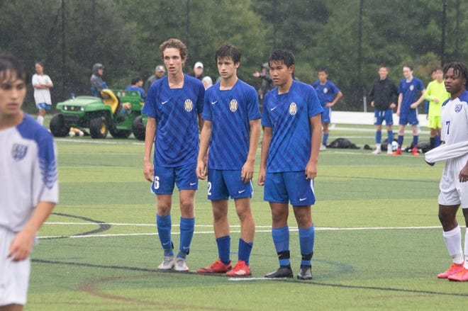 Junior Sam Shmukler, senior Kyler Maira and junior Caden Li line up for a corner kick against Bedford. (Courtesy Ed Palazzo)