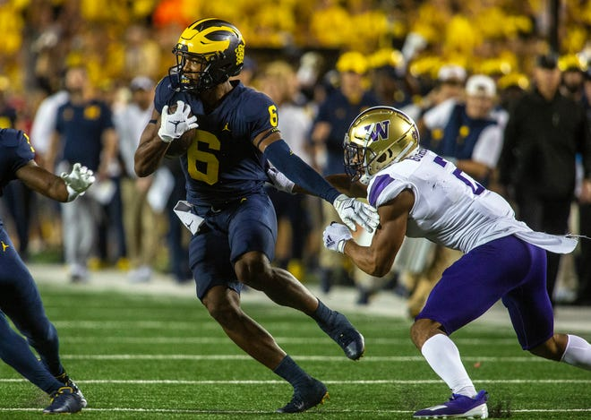 Michigan wide receiver Cornelius Johnson (6) rushes away from Washington defensive back Kyler Gordon, right, in the first quarter of an NCAA college football game in Ann Arbor, Mich., Saturday, Sept. 11, 2021. (AP Photo/Tony Ding)