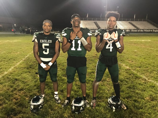 Winslow's Trey Thorpe, left, Hamas Duren, center, and Jacob Mitchell all had huge games as the Eagles beat Woodrow Wilson 32-30 on Saturday night.