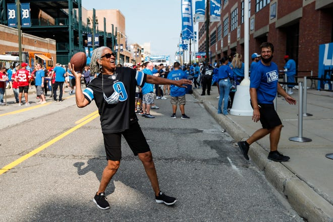 Detroit Lions fan Cynthia Lewis of Detroit throws a football at the Pride Plaza outside of Ford Field in Detroit before the opener vs. the San Francisco 49ers on Sunday, Sept. 12, 2021.