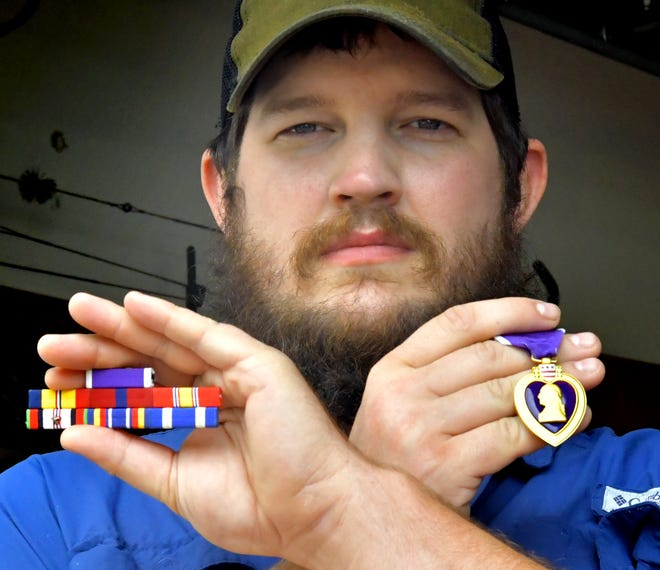 Marine Cpl. Adam Lanier poses with some of his military decorations, including a Purple Heart, at his home in Springettsbury Township Sunday, Sept. 12, 2021. Lanier was shot in the head while serving in Afghanistan in 2010. Bill Kalina photo
