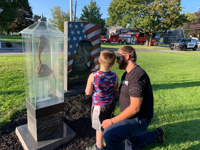 Spenser Seils and his son, Tucker, 6, are seen at the monuments of Sept. 11, 2001, during the 20th anniversary ceremony at the Canandaigua American Legion Post 256.
