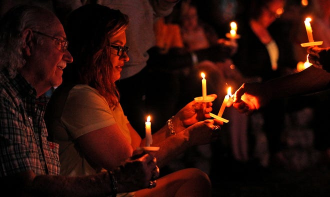 Audience members take part in a candle light vigil during the 20th anniversary ceremony of the 9/11 attacks at the Bill Aylor Sr. Memorial River Stage on Saturday, Sept. 11, 2021.
