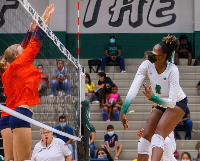 Connally's Naterah Moore, right, takes a swing against Glenn earlier this season. Moore had 13 kills and four blocks as the Cougars opened district play with a four-set win over Pflugerville Friday.