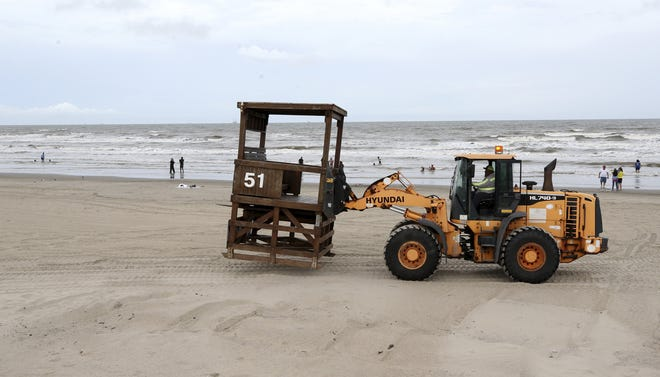 A worker removes a lifeguard tower from the beach in Galveston, Texas on Sunday, Sept. 12, 2021, as the Park Board of Trustees and the Galveston Island Beach Patrol prepare for Tropical Storm Nicholas. Nicholas is strengthening just off the Gulf Coast and could blow ashore in Texas as a hurricane as it brings heavy rain and floods to coastal areas from Mexico to storm-battered Louisiana.