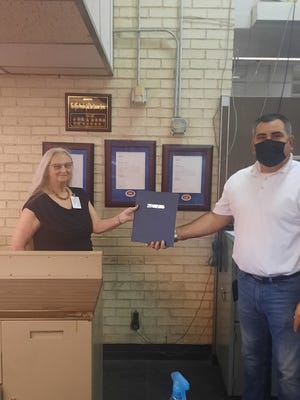 Diana Hockett, left, receives recognition from Bartlesville Postmaster Justin Wilson, on the final day of her 38-year career with USPS. Hockett retired in early September.