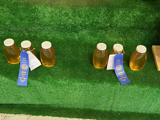 These blue ribbons in honey were won by Peggy  Garnes, left, and Richard  Sprague.
