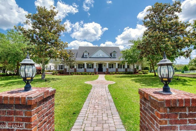 This luxurious retreat, with full-length front and back porches, is tucked away on a two-and-a-half-acre private lot in the Ormond Beach community of Riverbend Acres.