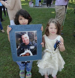 Adalynn McDonnell, 5, and her cousin, her four year old cousin Rosalia Allen, hold a picture of their uncle Brian McDonnell, following Hawley's 20th anniversary 9/11 ceremony. Adaylynn's mother Gina McDonnell said that Brian was an officer was New York Port Authority Emergency Response Team when he perished after he entered Tower 2 of the World Trade Center, just before it collapsed in the terrorist attacks of Sept. 11, 2001.