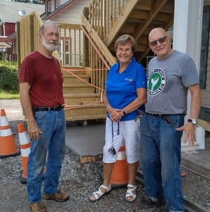 From left are Newfoundland Rotary members Roger Altemier, Kerry Nix and Max Feldman, in front of the emergency stairway built in back of the Newfoundland Area Public Library. The Rotary Club helped fund the building of the needed stairway. / Contributed image