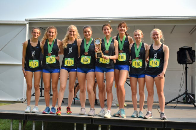 The Blue Springs South girls cross country team poses with the team trophy after capturing the Green Division title of the Forest Park XC Festival Saturday in St. Louis. Mya Trober, holding the trophy, finished fourth overall to lead the Jaguars.