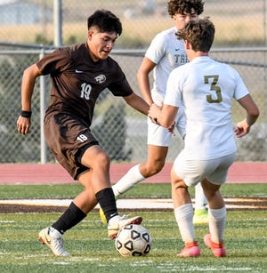 Garden City High School's Miguel Bustos, left, moves the ball upfield against Hays Aug. 31 at Buffalo Stadium. The Buffaloes finished in third place of the Goddard tournament on Saturday with a 3-0 victory over Rose Hill.