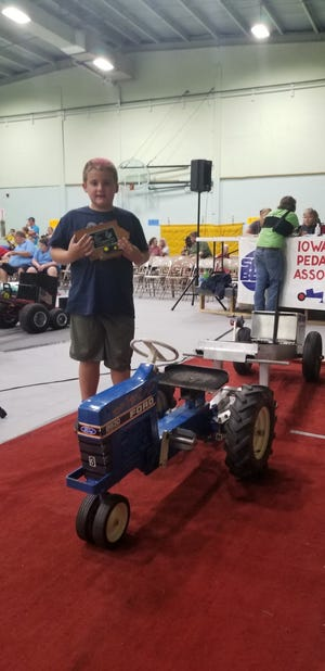 """Callan Finch, 7-years-old, peddled his way to 1st place at the 31st Annual Iowa State Pedal Tractor Pull Championships September 11, in Burt, IA. His pull was 33' 4"""". Callan is the son of Corey and Courtney Finch, rural Cambridge."""