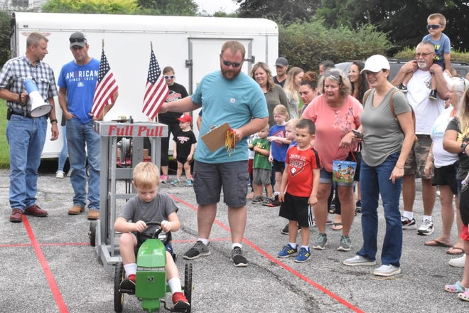 Four-year-old Nixon Gibbs of Orion digs in during Orion Fall Festival's pedal tractor pull on Saturday morning, Sept. 4, in the parking lot at Kirk, Huggins & Esterdahl Funeral Home.