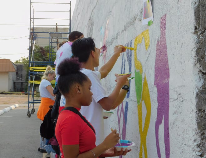 Sherman High School students prepare a mural site Saturday morning during a workshop in downtown Sherman. The mural project is being leg by  Mount Pleasant-based artist David Freeman and members of the community will be able to paint portions of the mural as a part of Sherman Arts Fest this weekend.