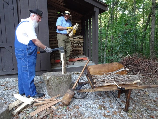 """Country Hawkins and Larry McKinley split and stack firewood """"free out of the woods."""" Notice Country's antique wooden wheelbarrow that is similar to the one Granny used on Bear Mountain."""