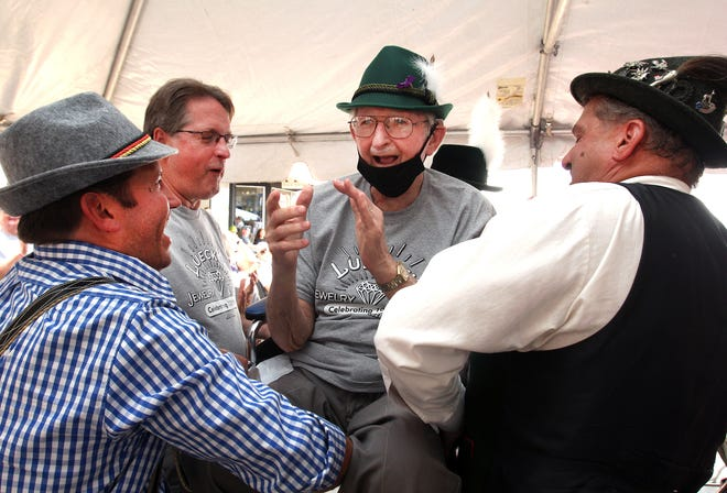 """Charlie Luecke, center, claps his hands as Bernie Luecke, left, Chuck Luecke, second from left, and Darryl Mertz, right, lift his chair for the singing of the German birthday song """"Hoch soll er/sie leben"""" during the 100th anniversary celebration of Luecke Jewelers on Saturday, Sept. 11, 2021, in downtown Freeport."""