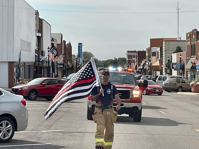 Chanhassen firefighter Doug Foote walks through downtown Montevideo on his 200-mile route.