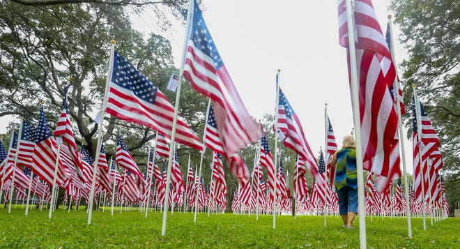 A volunteer walks through the Field of Valor installation at the former Mullet Festival grounds in Niceville. The flags honor service members from Florida who were killed in Iraq and Afghanistan.